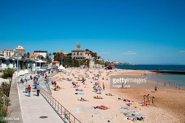 People at Tamariz beach with Estoril Castle