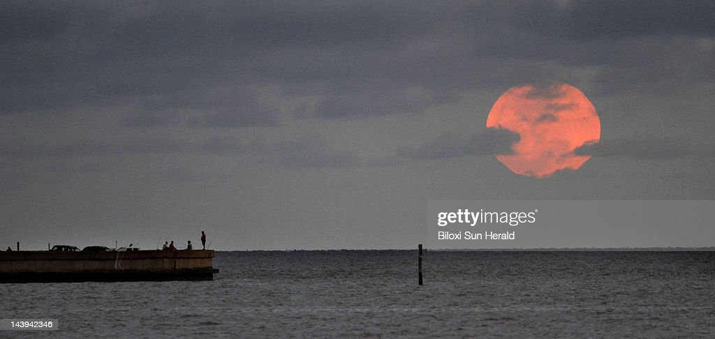 People at the old Broadwater Marina watches the Perigee Moon rise over the Mississippi Sound in Biloxi, Mississippi, on Saturday, May 5, 2012. This occurrence happens when the Moon is in its nearest approach to Earth.