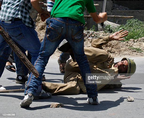 People attack a policeman on the street during a protest of the deaths of three civilians in clashes over the weekend on June 28 2010 in Srinagar...