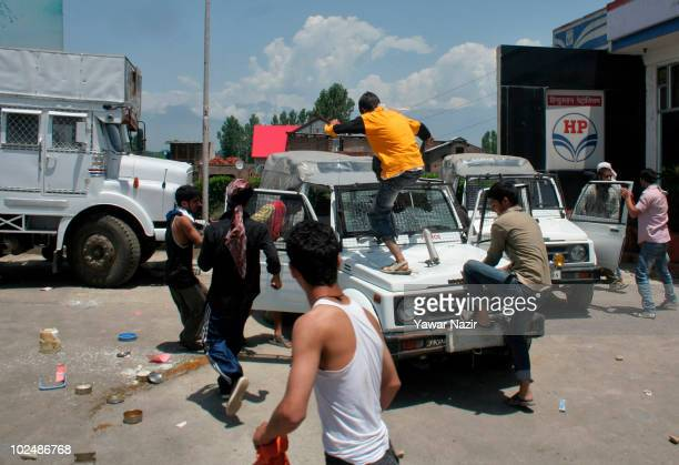 People attack an armored Indian police vehicle on the street during a protest of the deaths of three civilians in clashes over the weekend on June 28...