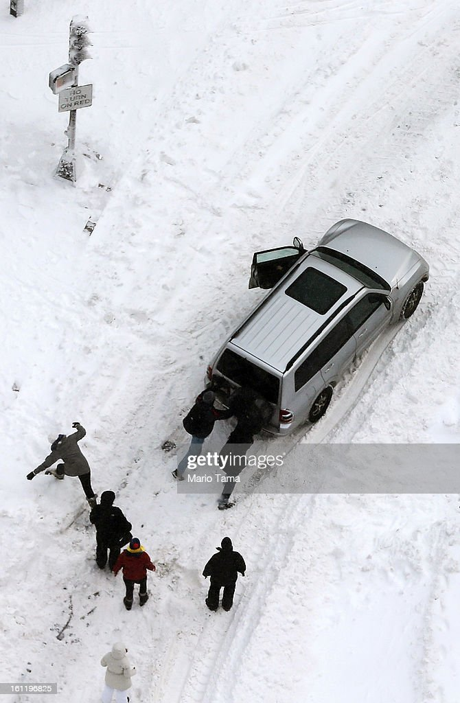 People attempt to push a stuck vehicle in the Back Bay neighborhood following a powerful blizzard on February 9, 2013 in Boston, Massachusetts. The storm knocked out power to 650,000 and dumped more than two feet of snow in parts of New England.