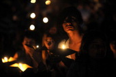 People attend a candle light vigil at Ciudad del Rio park as they stand in the dark during the Earth Hour on March 26 in Medellin Antioquia...