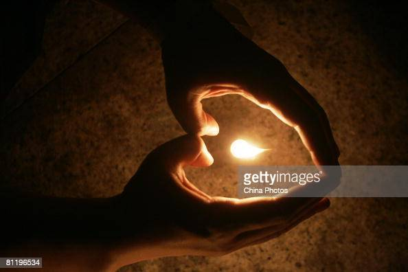 People attend a candle light vigil to pray for the survivors and the victims of an earthquake at the Renmin Square on May 21 2008 in Shanghai China...