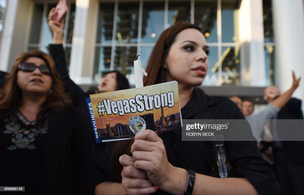 TOPSHOT - People attend a candlelight vigil at Las Vegas City Hall October 2, 2017, after a gunman killed at least 58 people and wounded more than 500 others when he opened fire on a country music concert in Las Vegas, Nevada late October 1, 2017. / AFP PHOTO / Robyn Beck