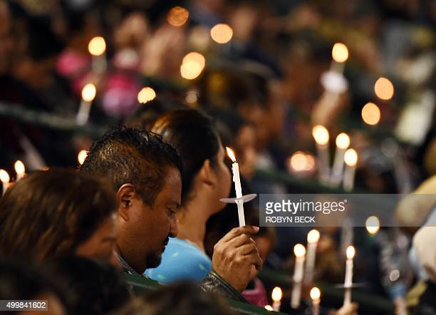 People attend a candlelight vigil at the San Manuel Stadium in San Bernardino California December 3 2015 for victims of the December 2 mass shooting...