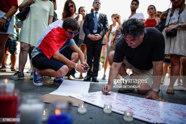 TOPSHOT People attend a candlelight vigil for the victims of truck attack in Nice France at Washington Square Park in New York on July 16 2016 A...