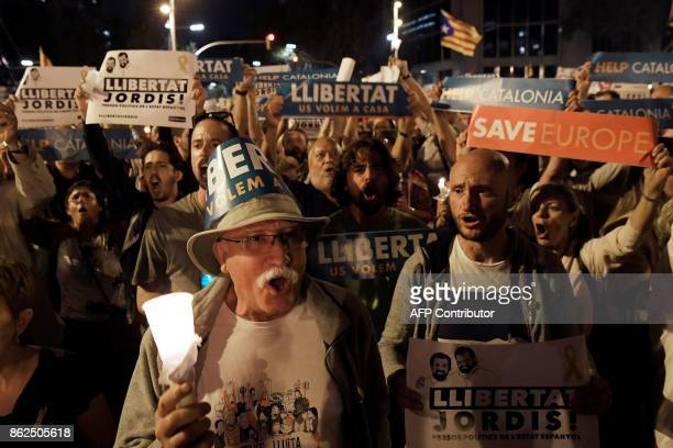 People attend a candlelit demonstration in Barcelona against the arrest of two Catalan separatist leaders on October 17 2017 Catalonia braced for...