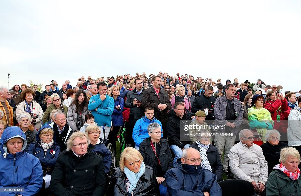 People attend a ceremony at Ovillers-la-Boisselle on July 1, 2016 to commemorate the centenary of the battle of the Somme, one of the deadliest of the World War I (1.2 million killed, missing and wounded in five months), next to the Lochnagar Crater, a mine crater created after a British mine exploded, marking the launch of the British offensive against the German lines. / AFP / FRANCOIS