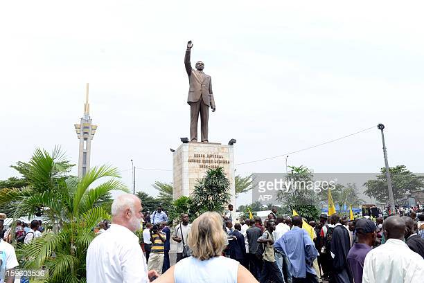 People attend a ceremony for former Congolese President Patrice Lumumba in front of his statue in Limete Kinshasa on the 42nd anniversary of his...
