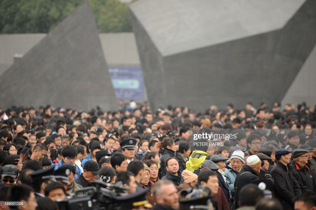 People attend a ceremony for victims to mark the 75th anniversary of the Nanjing massacre at the Memorial Museum in Nanjing on December 13, 2012. Air raid sirens sounded in the Chinese city of Nanjing on December 13 as it marked the 75th anniversary of the mass killing and rape committed there by Japanese soldiers -- with the Asian powers' ties at a deep low. AFP PHOTO/Peter PARKS