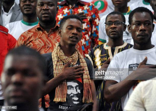 People attend a ceremony marking the 30th anniversary of the death of late Burkina Faso's leader Thomas Sankara on October 15 2017 in Ouagadougou...