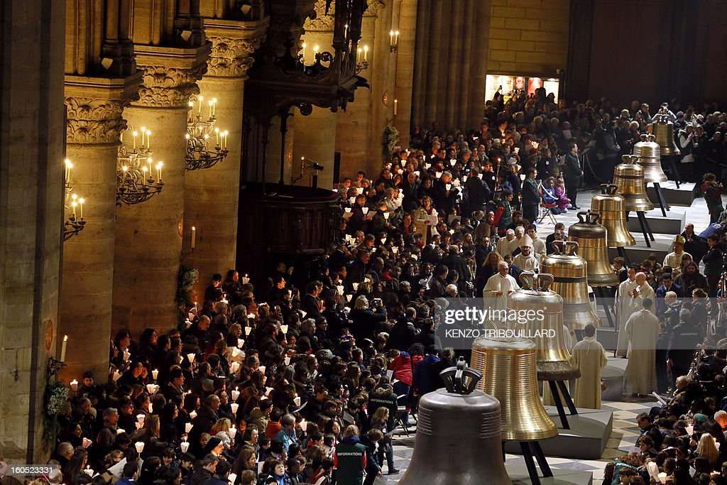 People attend a ceremony to inaugurate nine new church bells on February 2, 2013 at Notre-Dame de Paris Cathedral in Paris. Hundreds of pupils attend the ceremony during a jubilee. AFP PHOTO KENZO TRIBOUILLARD