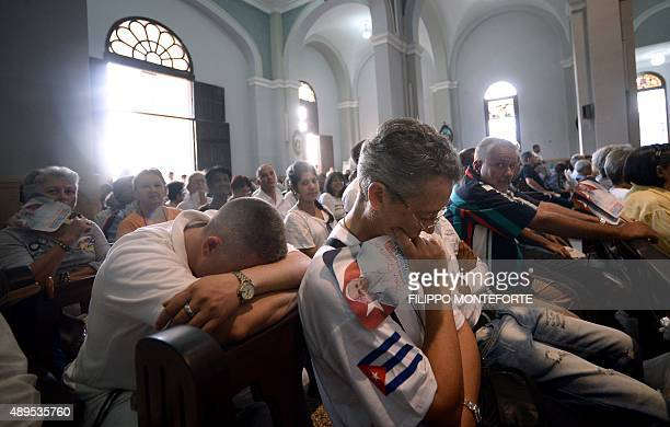 People attend a mass officiated by Pope Francis at the basilica to Our Lady of Charity of El Cobre the patron saint of Cuba a mixedrace Mary that...