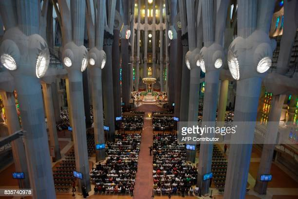 People attend a mass to commemorate victims of two devastating terror attacks in Barcelona and Cambrils at the Sagrada Familia church in Barcelona on...