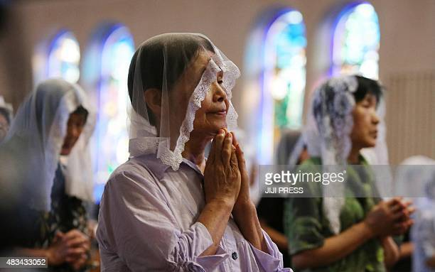 People attend a morning mass for victims of the World War II atomic bombing of Nagasaki at the city's Urakami cathedral on August 9 2015 Japan on...