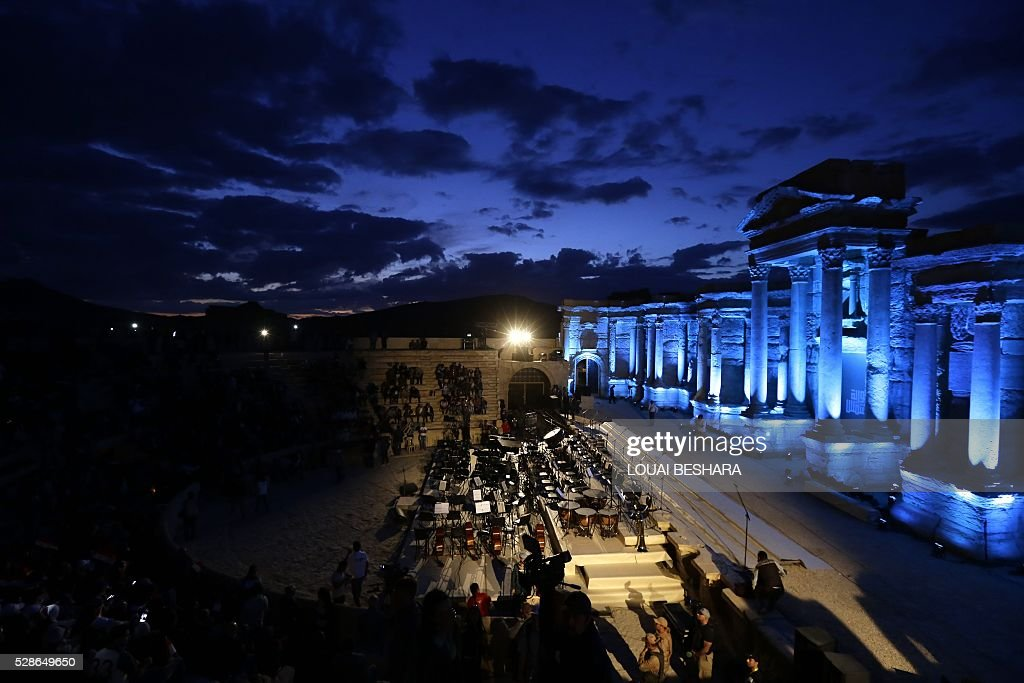 People attend a music concert in the ancient theatre of Syria's ravaged Palmyra on May 6, 2016 following its recapture by regime forces from the Islamic State group fighter. Syrian troops backed by Russian air strikes and special forces on the ground recaptured UNESCO world heritage site Palmyra from Islamic State (IS) group fighters in March 2016. BESHARA