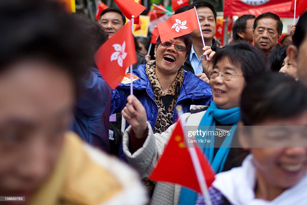 People attend a New Year's Day rally to express their support for Hong Kong's Chief Executive CY Leung prior to a demonstration for his resignation on January 1, 2013 in Hong Kong, Hong Kong. Tens of thousands of protesters took to the streets of Hong Kong calling for the city's embattled leader to quit and demanding greater democracy 15 years after it returned to Chinese rule.