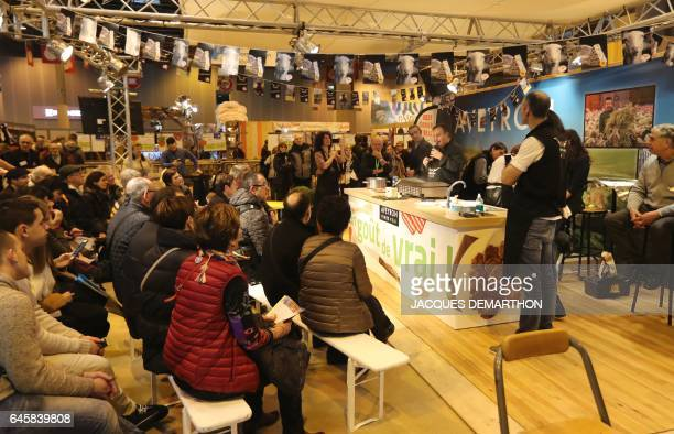 People attend a presentation of beef farm meat products from the Aubrac region at the stand of the Aveyron department on February 27 2017 at the...