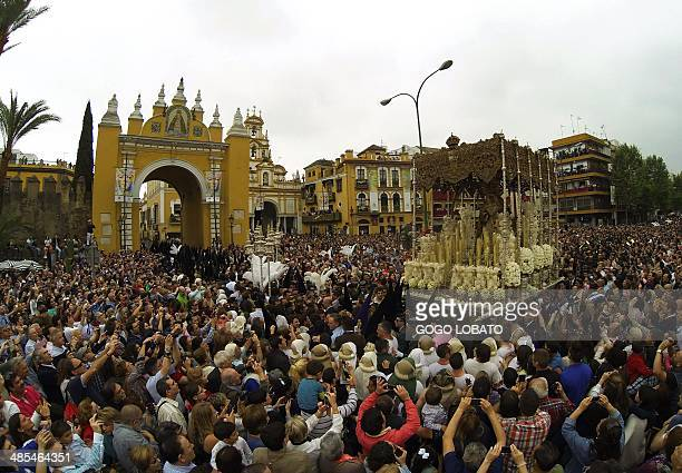 People attend a procession of 'La Macarena' brotherhood during a Holy Week procession in Sevilla on April 18 2014 Christian believers around the...