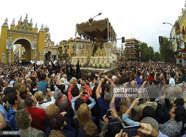 People attend a procession of 'La Macarena' brotherhood during the Holy Week in Sevilla on April 18 2014 Christian believers around the world mark...