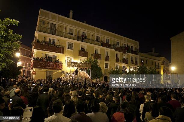 People attend a procession of the penitents of 'Los Gitanos' brotherhood during the Holy Week in Sevilla on April 18 2014 Christian believers around...