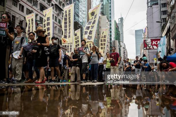 TOPSHOT People attend a protest march in Hong Kong on July 1 coinciding with the 20th anniversary of the city's handover from British to Chinese rule...