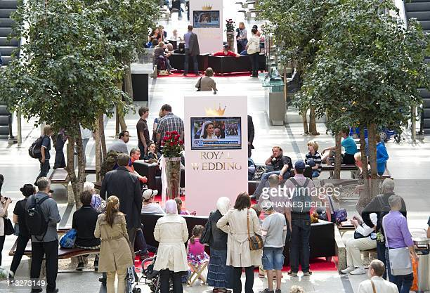 People attend a public viewing of the royal wedding of Britain's Prince William and his wife Kate Middleton on April 29 2011 in a shopping mall in...