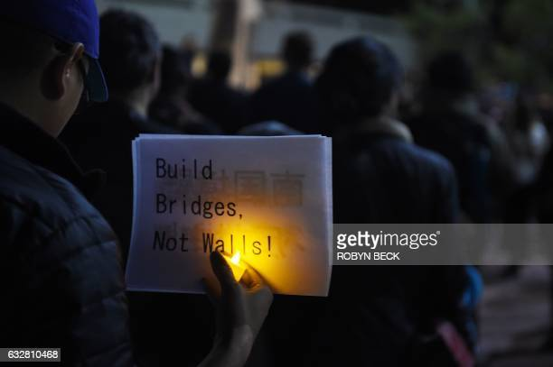 TOPSHOT People attend a rally and candlelight vigil in Los Angeles California January 26 to protest against Islamophobia and US President Donald...