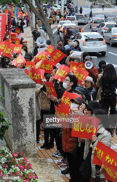 People attend a rally denouncing the relocation of a US military base in front of the Okinawa prefectural office in Naha southern Japan on December...