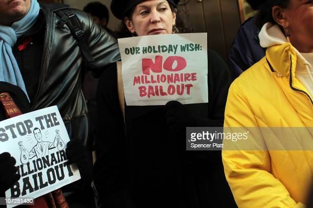 People attend a rally outside of the office of Sen Charles Schumer to protest an extension of tax breaks for the wealthiest two percent of Americans...
