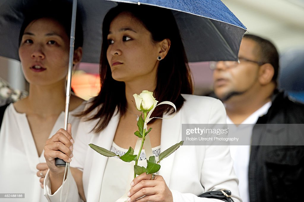 People attend a silent march for Jenny Loh and Fan Piopo the owners of the Asian Glories restaurant and Jenny's mother who were killed in the downed Malaysian Airlines flight MH17 on July 21, 2014 in Rotterdam, Netherlands. The aircraft was travelling from Amsterdam to Kuala Lumpur when it crashed killing all 298 on board including 80 children. The aircraft was allegedly shot down by a missile and investigations continue over the perpetrators of the attack.