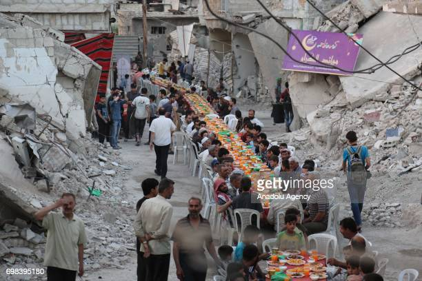 People attend an iftar dinner organized by Adale Relief Foundation around the debris of buildings at Douma district which is under blockade for last...