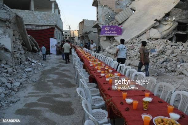 People attend an iftar dinner organized by Adale Relief Foundation around the wreckage of buildings at Douma district which is under blockade for...