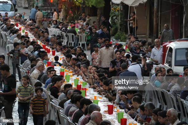 People attend an iftar dinner organized by Al Rahma Charity Association around the wreckage of buildings at Arbin district which is under blockade...