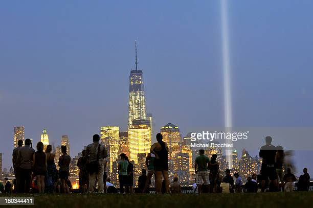 People attend an interfaith memorial as the 'Tribute in Light' shines from the Manhattan skyline next to One World Trade Center to commemorate all...