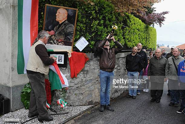 People attend the commemoration ceremony for the death of Italian dictator Benito Mussolini and his mistress Claretta Petacci in front of a headstone...