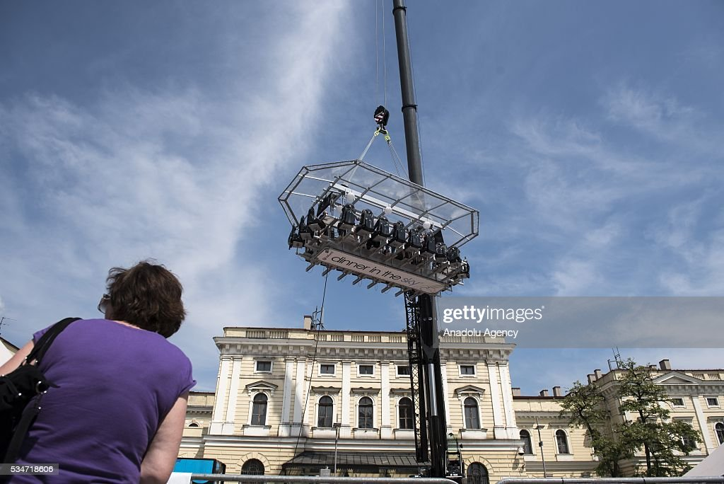 People attend the event Dinner in the Sky at the Plac Jezioranskiego, Krakow, Poland on MAY 27, 2016. Dinner In The Sky is a unique event and takes place at a table suspended at a height of 50 meters above the ground. Dinner in the Sky is a prestigious event which has been recognized in more than 30 countries such as the United States, Canada, England, France, Portugal and others.