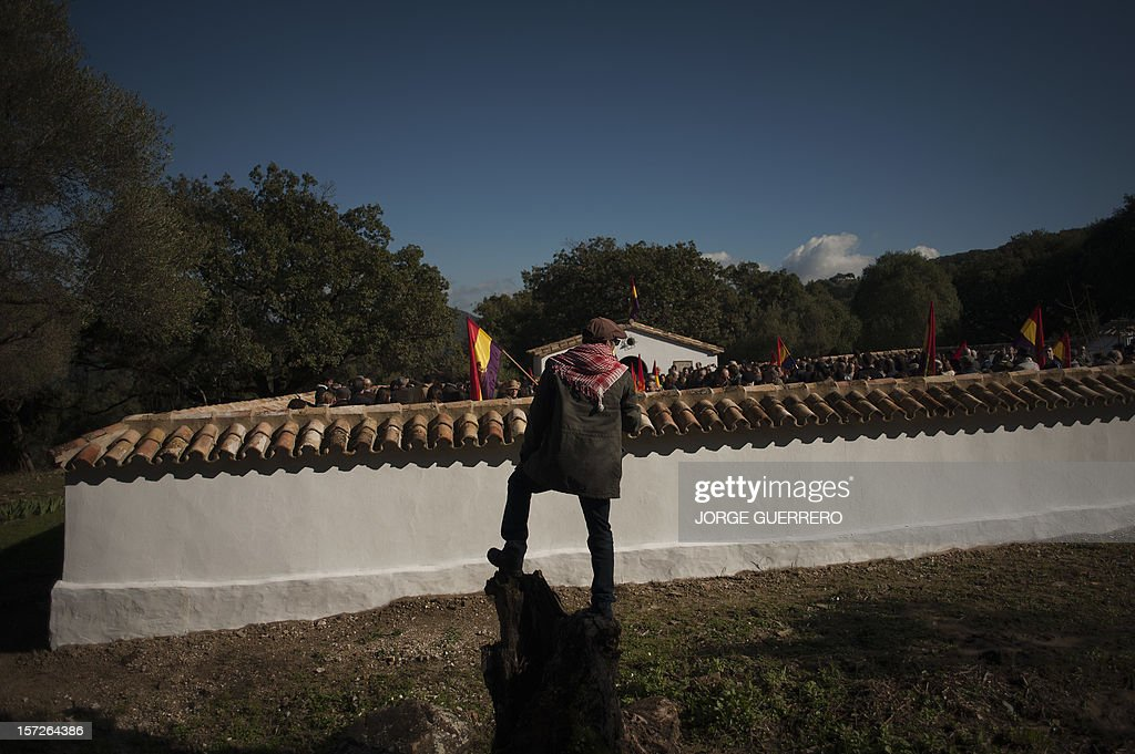 People attend the funeral ceremony for 28 people executed during the Spanish Civil War at La Sauceda Cemetery in Cortes de la Frontera on December 1, 2012. Twenty-eight people, seven women and 21 men, of the hundreds who were tortured and executed by the forces of Francisco Franco at the 'El Marrufo Estate' in Cadiz during the Spanish Civil war, received a proper burial today, 76 years after their bodies, all shot, were thrown into mass graves. AFP PHOTO / JORGE GUERRERO