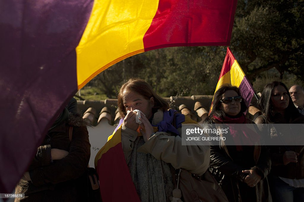 People attend the funeral ceremony for 28 people executed during the Spanish Civil War at La Sauceda Cemetery in Cortes de la Frontera on December 1, 2012. Twenty-eight, seven women and 21 men, of the hundreds of people who were tortured and executed by the forces of Francisco Franco at the 'El Marrufo Estate' in Cadiz during the Spanish Civil war, received a proper burial today, 76 years after their bodies, all shot, were thrown into mass graves. AFP PHOTO / JORGE GUERRERO