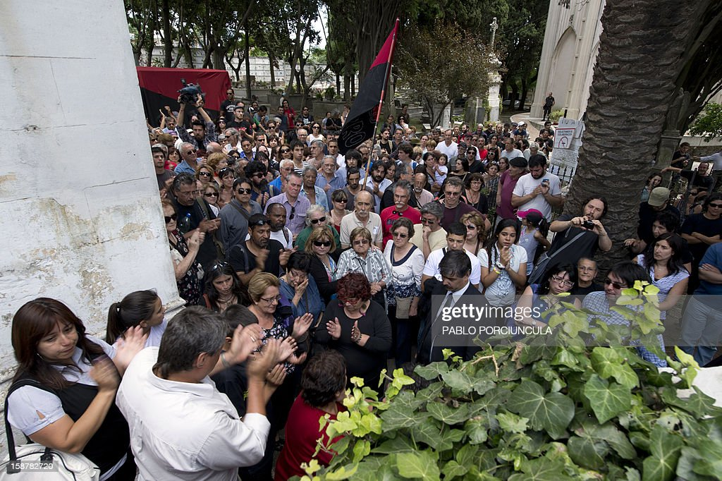 People attend the funeral of Uruguayan anarchist Alberto Mechoso --disappeared in Buenos Aires in 1976 during Argentina's military dictatorship-- in Montevideo on December 28, 2012. The Uruguayan Government gave the remains of Mechoso to his relatives after being identified in Argentina. Mechoso was detained in September 26, 1976 and he was seen for the last time at the clandestine detention centre Automotoras Orletti on that year. AFP PHOTO/Pablo PORCIUNCULA