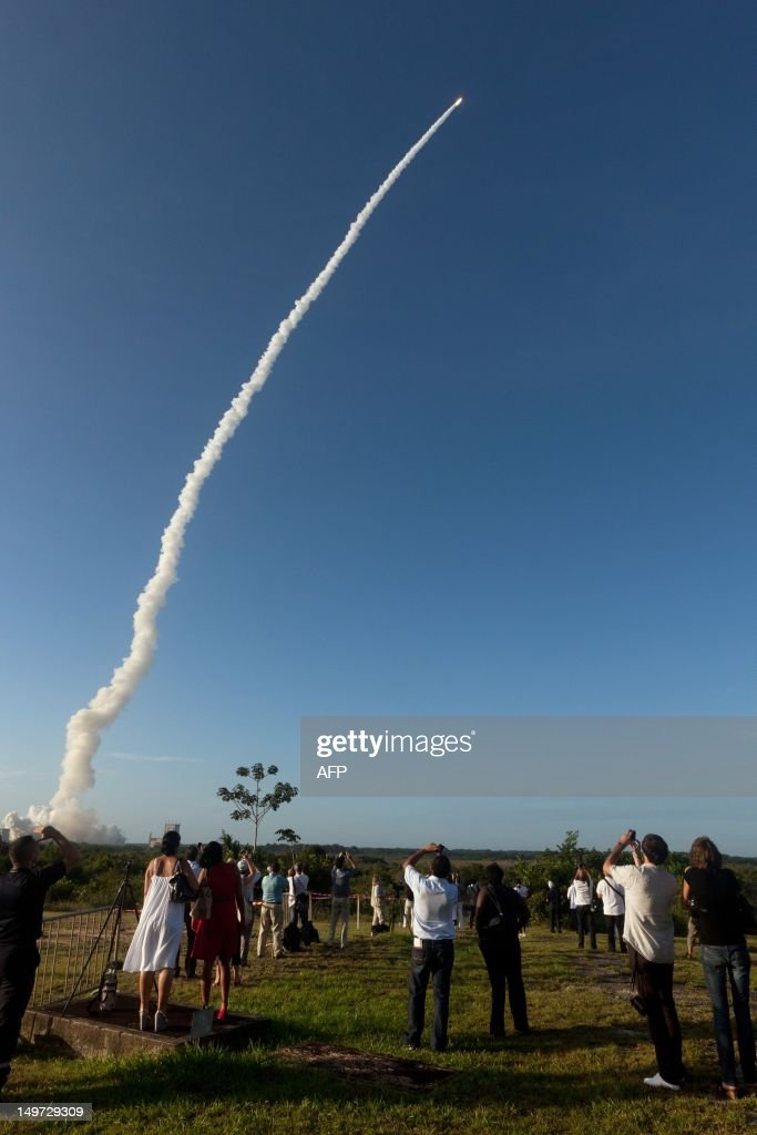 People attend the launch of An Ariane-5 rocket, carrying two telecommunication satellites and blasting off from the European space centre of Kourou, French Guiana on August 2, 2012. It will eventually place into orbit two geostationary telecommunication satellites -- Intelsat-20 for international satellite operator Intelsat, and HYLAS 2 for European operator Avanti Communications. Intelsat-20, which weighs more than six tonnes, will provide a large number of telecommunication, video, telephone and data transmission services in Europe, the Middle East, Russia and Asia.