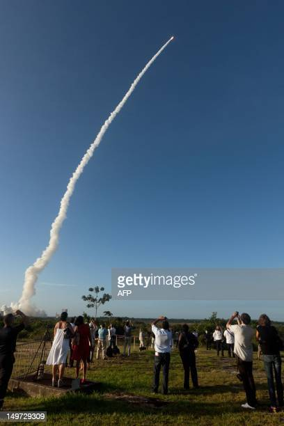 People attend the launch of An Ariane5 rocket carrying two telecommunication satellites and blasting off from the European space centre of Kourou...