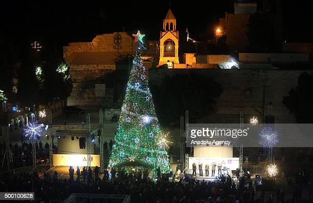 People attend the lighting of a Christmas tree in Manger Square outside the Church of the Nativity in the West Bank town of Bethlehem on December 5...