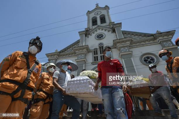 People attend the mass funeral of victims of a mudslide caused by heavy rains in Mocoa Putumayo department southern Colombia on April 4 2017 The...
