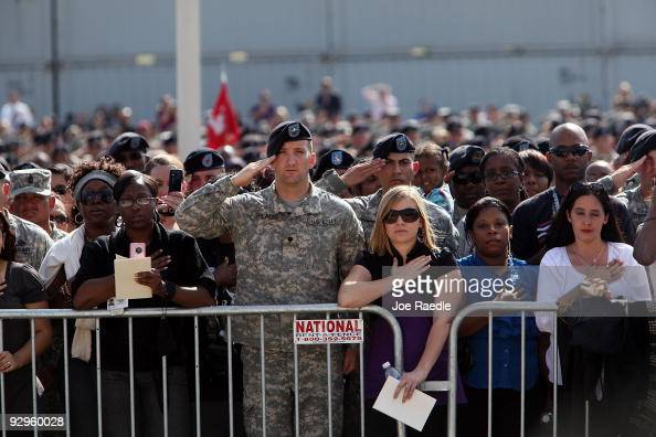 People attend the memorial service that US President Barack Obama and first lady Michelle Obama are attending for the thirteen victims of the...
