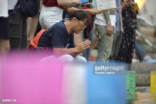 People attend the Peace Message Lantern Floating Ceremony held to console the souls of the ABomb victims after the Hiroshima Peace Memorial Ceremony...