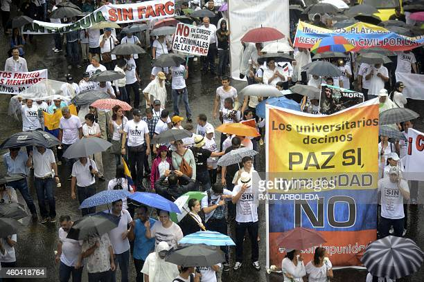 People attend the 'Peace without Impunity' march against the current peace talks with FARC rebels in Medellin a sign reads 'University students say...