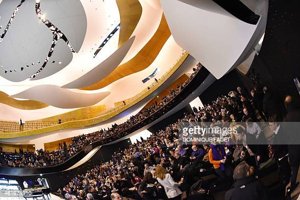 People attend the performance of Chinese pianist Lang Lang accompanied by 101 young pianists during open house at the 'Philharmonie de Paris' concert...