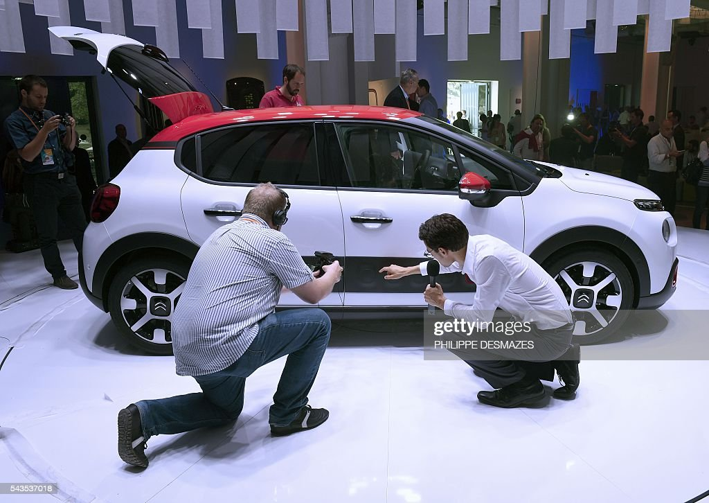 People attend the presentation of the new Citroen C3 of French automobile manufacturer, in Lyon on June 29, 2016. / AFP / PHILIPPE