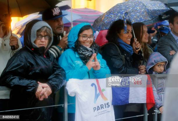 People attend the unveiling of the Olympic rings on the esplanade of Trocadero in front of the Eiffel tower after the official announcement of the...